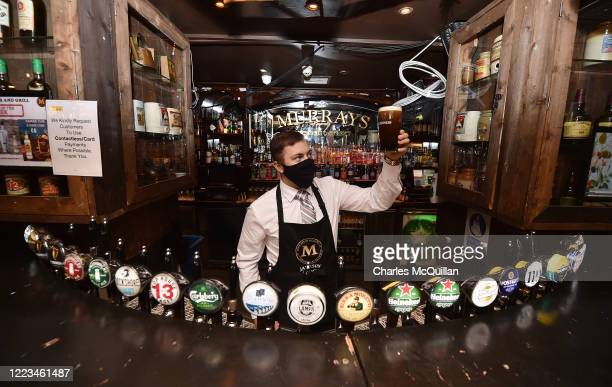 Barman in Murrays pub on Grafton street checks the head on a pint of Guinness on June 29, 2020 in Dublin, Ireland. Restaurants, pubs, cafes and...