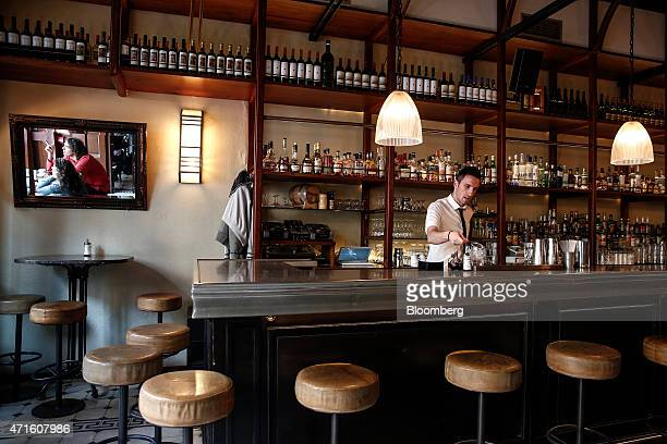 A barman makes drinks at the Osterman barrestaurant once a fabric store in the Agia Irini district of Athens Greece on Saturday April 25 2015 The...