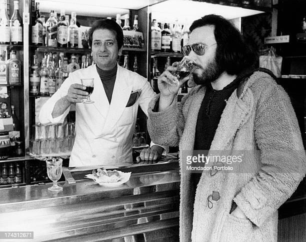 A barman offering a drink to Italian singer and songwriter Antonello Venditti Rome 1970s