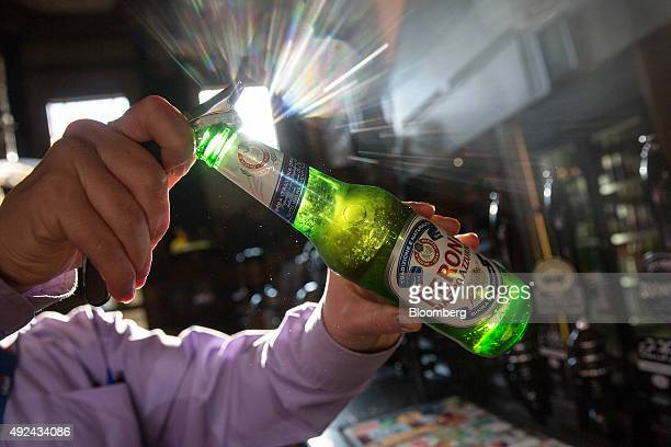 A barman opens a bottle of Peroni beer brewed by SABMiller Plc in The Capitol a JD Wetherspoons Plc public house in this arranged photograph in...