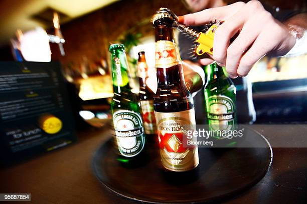 A barman opens a bottles of Dos Equis and Heineken beer at a public house in London UK on Monday Jan 11 2010 Heineken NV agreed to buy the beer...