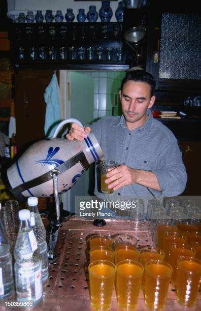 A barman pouring apple wine from a large jug in a bar called Germania