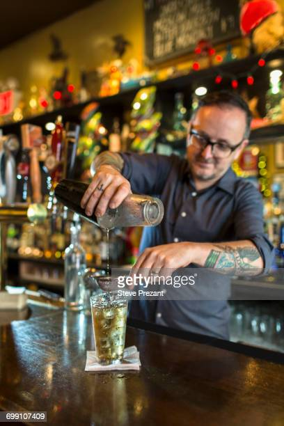 Barman pouring cocktail into glass at public house counter