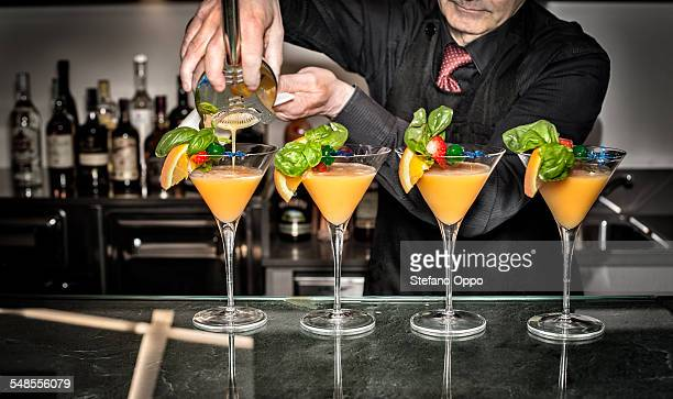 Barman pouring cocktails, mid section