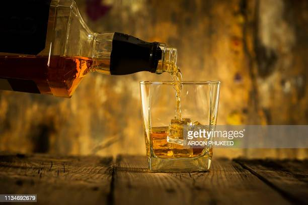 barman pouring whiskey in front of whiskey glass and bottles on black table with whiskey and ice on a glass table - rum stock pictures, royalty-free photos & images