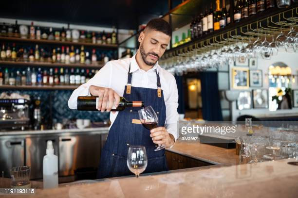 barman pouring wine into a glass - apron stock pictures, royalty-free photos & images