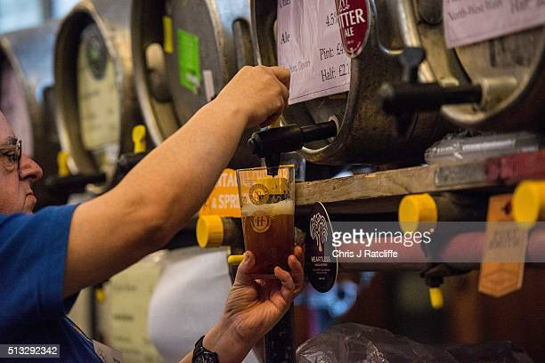 A barman pours an ale for a customer at the London Drinker Beer and Cider Festival at the Camden Centre on March 2 2016 in London England The event...