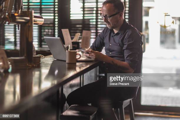 Barman reading smartphone texts at public house counter