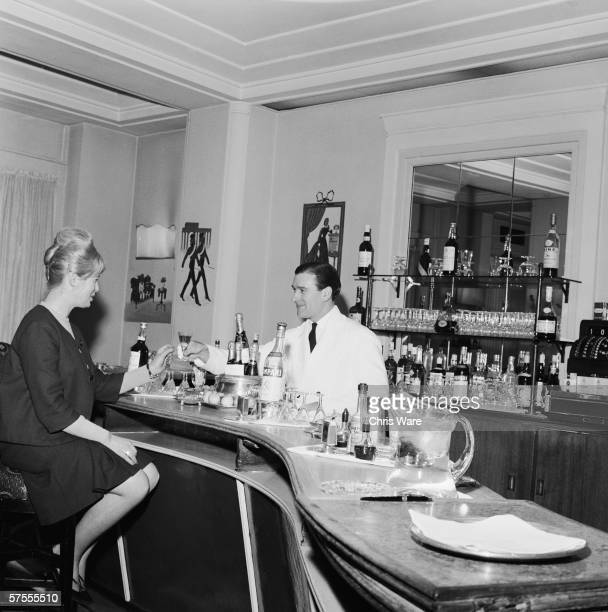A barman serves a drink to a female customer at the Ritz Hotel in London 29th May 1963