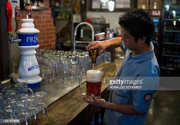 A barman serves Mexican craft beer in a bar in Mexico City on July 20 2012 Producers of handcrafted beer make their way in Mexico following the...