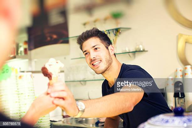 Barman serving a ice cream to customer