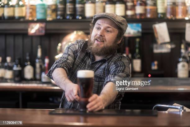 barman serving beer from bar in traditional irish public house - sigrid gombert stock-fotos und bilder