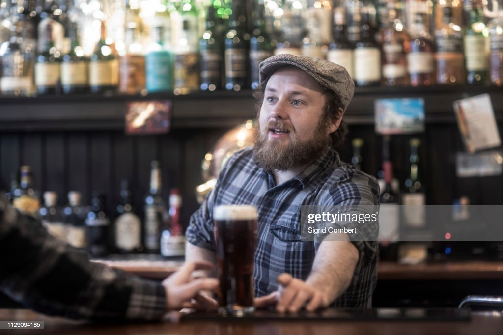 Barman serving beer to customer at bar in traditional Irish public house : Stock-Foto