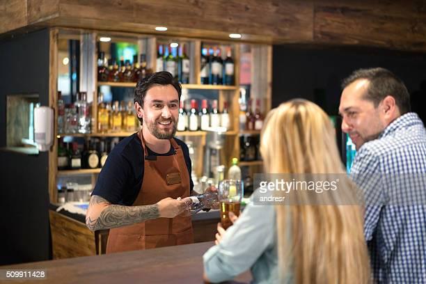 Barman serving couple at the bar