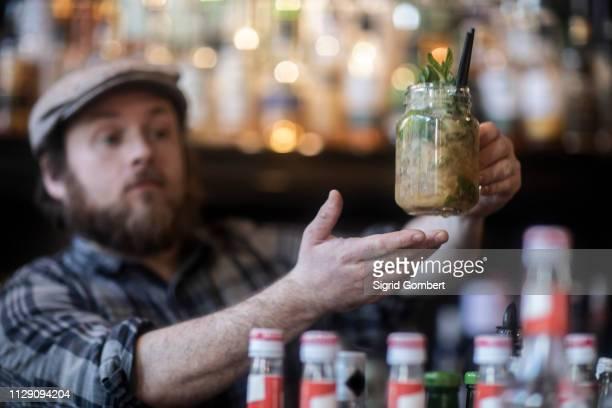 barman serving jar glass cocktail in traditional irish public house - sigrid gombert photos et images de collection