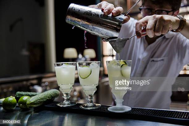 A barman uses a sieve as he prepares a green beast absinthe cocktail at Pernod Ricard SA's absinthe distillery in Thuir France on Wednesday June 8...