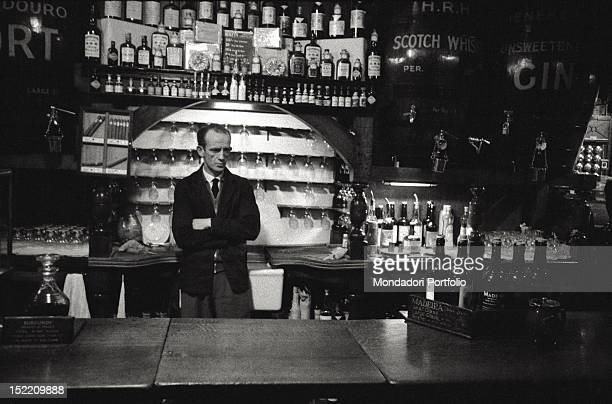 A barman with crossed arms is standing behind the bar of his pub waiting to serve his customers Behind the man various bottles London 1957