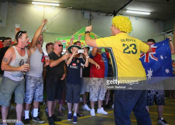 Barmy Army member throws beer as an Australian supporter sings during day one of the First Ashes Test match between Australia and England at The...