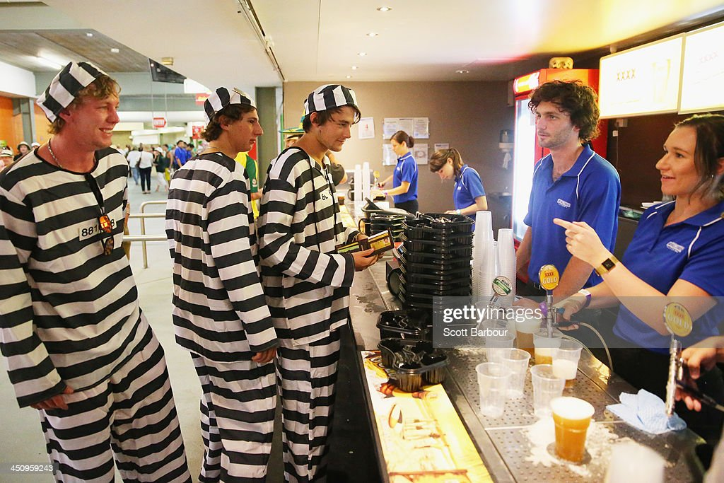 Barmy Army members dressed as convicts wait in line to purchase beer during day one of the First Ashes Test match between Australia and England at The Gabba on November 21, 2013 in Brisbane, Australia. The Barmy Army is a group of English cricket fans which arranges touring parties for some of its members to support the English cricket team on overseas tours, as well as followers of the team who join in with match day activities in the crowd, but do not travel as part of an organised tour.