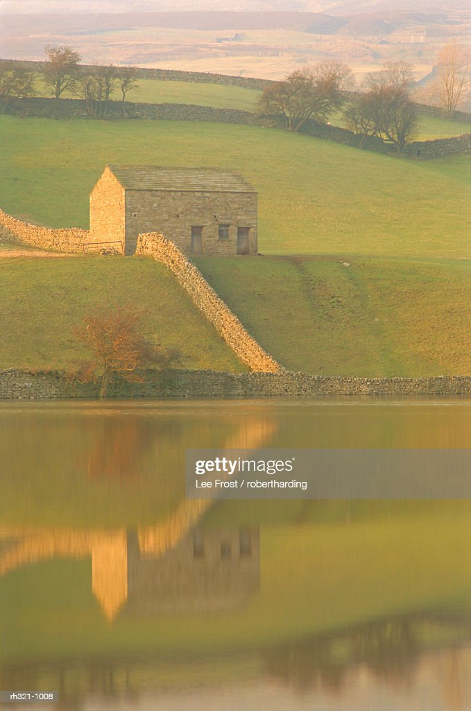 Barn and wall reflected in water at dusk, near Muker, Yorkshire Dales National Park, North Yorkshire, England, UK, Europe : Stockfoto