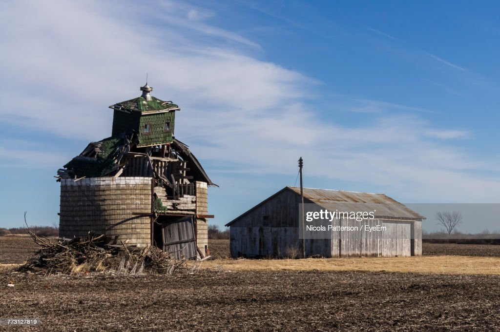 Barn By Abandoned Built Structure On Field Against Sky : Stock Photo