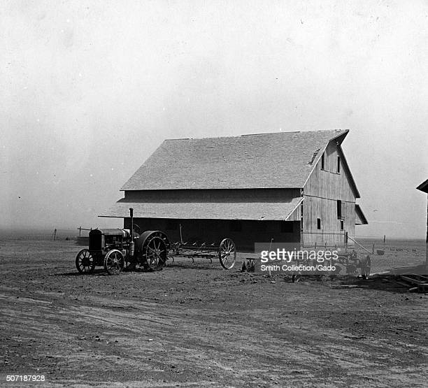 Barn on a farm in Kansas during the dustbowl era, surrounding by bleak terrain with several tractors parked in front of the barn, 1935. From the New...