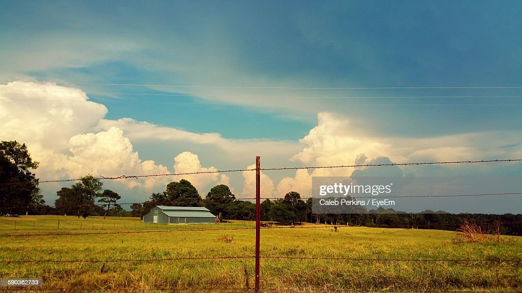 Barn On Field With Barbed Wire Fence Against Sky Stock Photo | Getty ...
