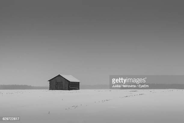 barn on snow covered field against clear sky - heinovirta stock photos and pictures