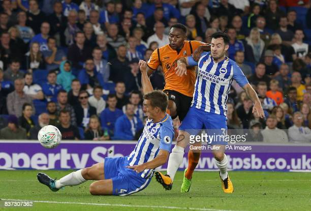 Barnet's JeanLouis Akpa Akpro is challenged by Brighton and Hove Albion's Uwe Hunemeier and Richie Towell as he shoots during the Carabao Cup Second...