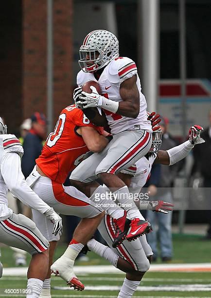 Barnett of the Ohio State Buckeyes leaps over Spencer Harris of the Illinois Fighting Illini to intercept a pass at Memorial Stadium on November 16,...