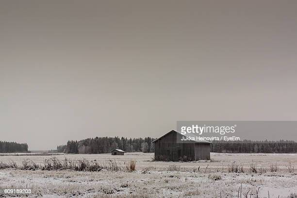 barns on field against sky during winter - heinovirta stock photos and pictures