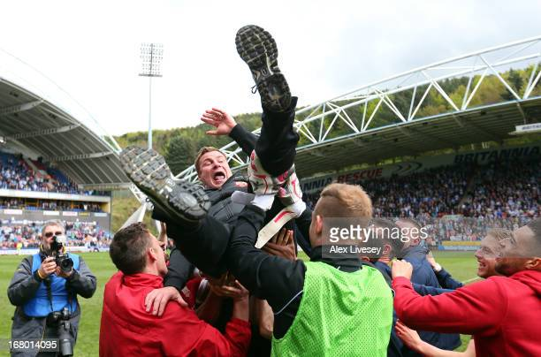 Barnsley manager David Flitcroft is thrown into the air by his players as they celebrate survival at the end of the npower Championship match between...