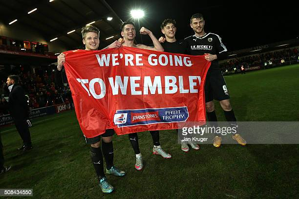 Barnsley players celebrate victory by posing with a flag during the Johnstone's Paint Trophy northern section semi final second leg match between...