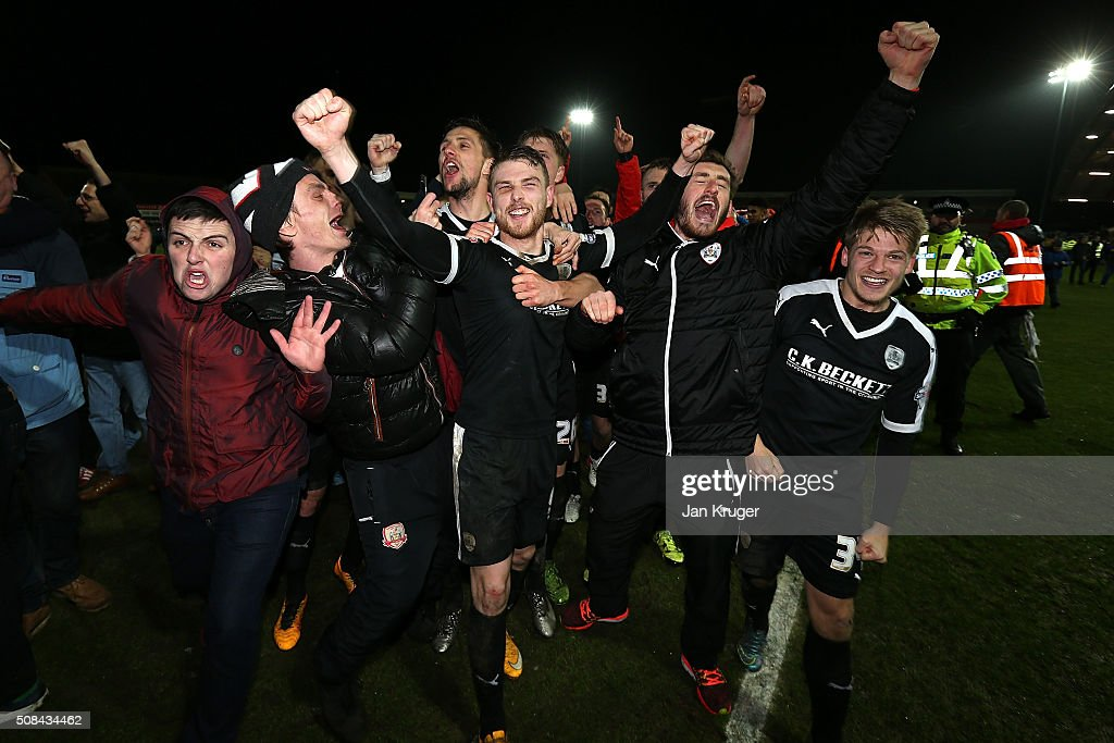 Barnsley players celebrate with fans on the pitch after winning the penalty shoot out during the Johnstone's Paint Trophy northern section semi final second leg match between Fleetwood Town and Barnsley at Highbury Stadium on February 4, 2016 in Fleetwood, England.