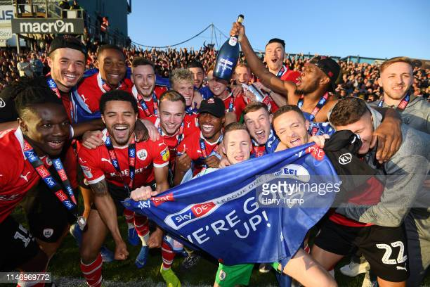Barnsley players pose for a photo as they celebrate earning promotion following the Sky Bet League One match between Bristol Rovers and Barnsley at...