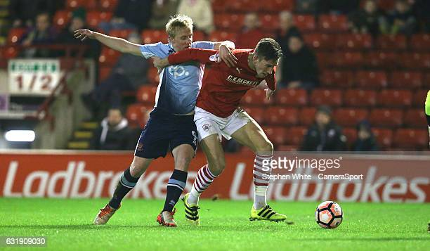 Barnsley's Angus MacDonald shields the ball from Blackpool's Mark Cullen during the Emirates FA Cup Third Round Replay match between Barnsley and...