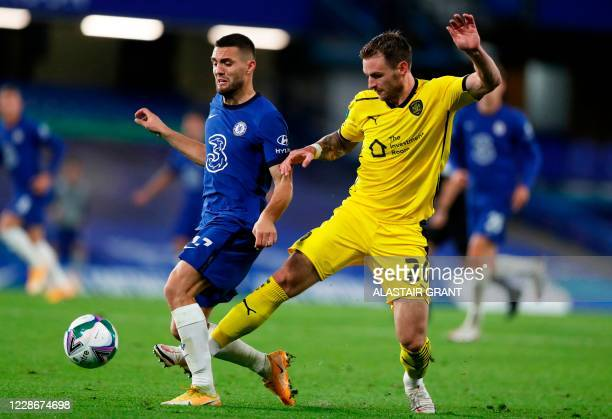 Barnsley's Austrian defender Michael Sollbauer fouls Chelsea's Croatian midfielder Mateo Kovacic during the English League Cup third round football...