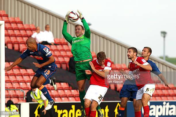 Barnsley's Ben Alnwick catches cleanly under pressure from Blackpool's Alex JohnBaptiste during the npower Championship match between Barnsley and...