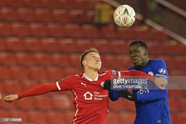 Barnsley's English striker Cauley Woodrow vies with Chelsea's French defender Kurt Zouma during the English FA Cup fifth round football match between...