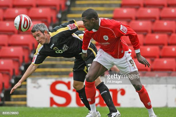 Barnsley's Kayode Odejayi and Cardiff City's Kevin McNaughton during the CocaCola Football League Championship match at the Oakwell Ground Barnsley