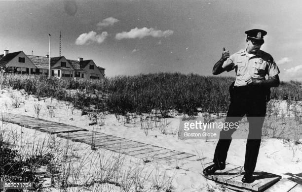 Barnstable police officer keeps beachgoers from entering the grounds of the Kennedy compound in Hyannisport Mass 1986