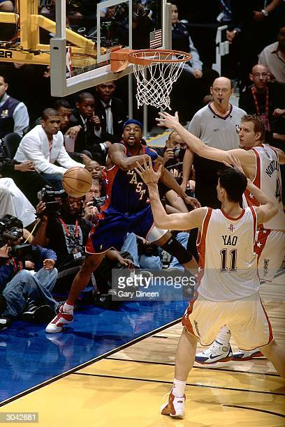 Baron Davis of the Eastern Conference AllStars passes against Yao Ming and Dirk Nowitzki of the Western Conference AllStars during the 2004 AllStar...