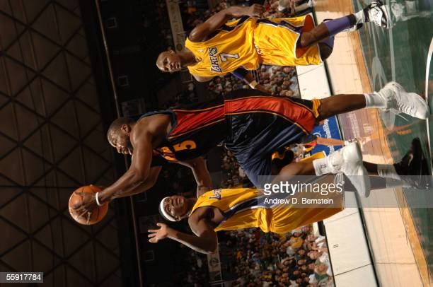 Baron Davis of the Golden State Warriors drives for a shot attempt against Smush Parker and Lamar Odom of the Los Angeles Lakers during a preseason...