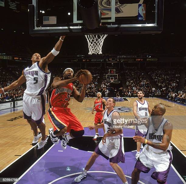 Baron Davis of the Golden State Warriors drives to the basket against Maurice Evans and Darius Songaila of the Sacramento Kings at ARCO Arena on...