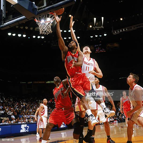 Baron Davis of the Golden State Warriors takes the layup against Yao Ming of the Houston Rockets during the game on April 5 2005 at The Arena in...
