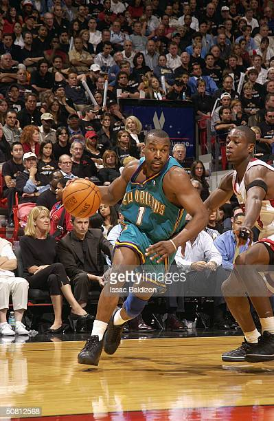 Baron Davis of the New Orleans Hornets drives by Dwyane Wade of the Miami Heat in Game 2 of the Eastern Conference Quarterfinals during the 2004 NBA...
