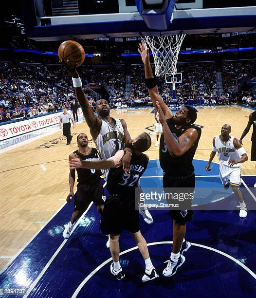 Baron Davis of the New Orleans Hornets drives to the basket against Fred Hoiberg and Oliver Miller of the Minnesota Timberwolves during the game at...