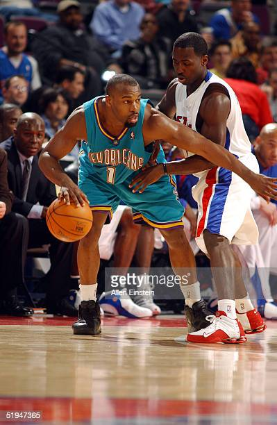 Baron Davis of the New Orleans Hornets posts against Anthony Goldwire of the Detroit Pistons drives against on January 12, 2005 during their game at...