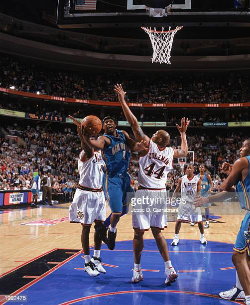Baron Davis of the New Orleans Hornets takes the ball up against Derrick Coleman of the Philadelphia 76ers in Game 5 of the Eastern Conference...