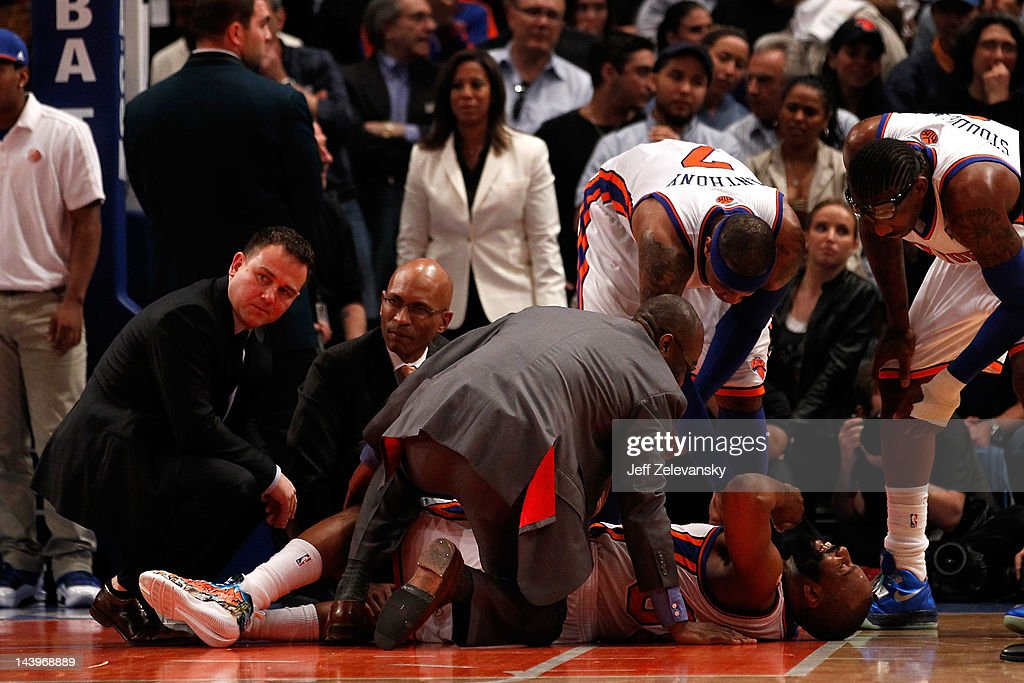 Baron Davis #85 of the New York Knicks is tended to by the team medical staff as players Carmelo Anthony #7 and Amare Stoudemire #1 after Davis injured his knee in the third quarter against the Miami Heat in Game Four of the Eastern Conference Quarterfinals in the 2012 NBA Playoffs on May 6, 2012 at Madison Square Garden in New York City.